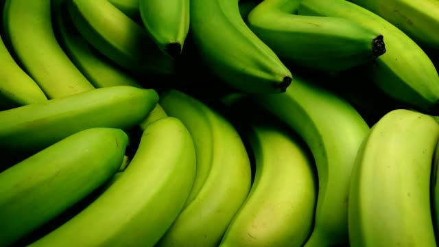 芸術的な照明で渡すバナナ房 - 熟していない点の映像素材/bロール