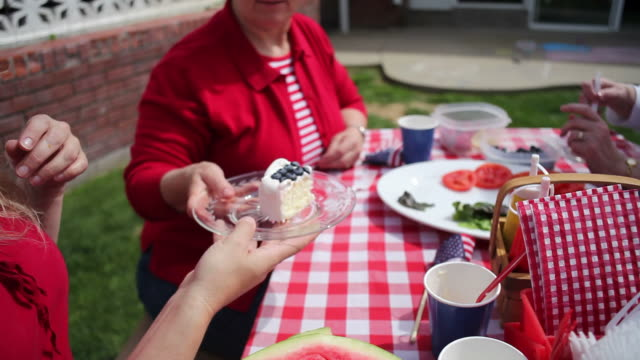 Passing cake at 4th of July party  family 4th of july stock videos & royalty-free footage