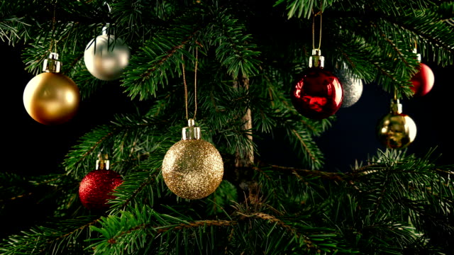 Passing Christmas Tree With Baubles Tracking shot moving slowly past a Christmas tree decorated with red, silver and gold baubles christmas ornament stock videos & royalty-free footage