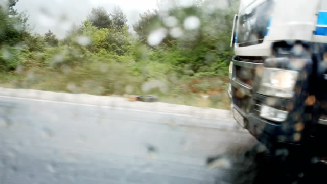 passing lorry truck on very rainy highway. detail of wheel over water drops at car window - truck tire video stock e b–roll