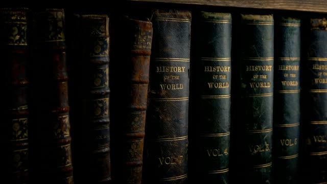 stockvideo's en b-roll-footage met passeren van de oude leer gebonden boeken op de plank - boekenkast