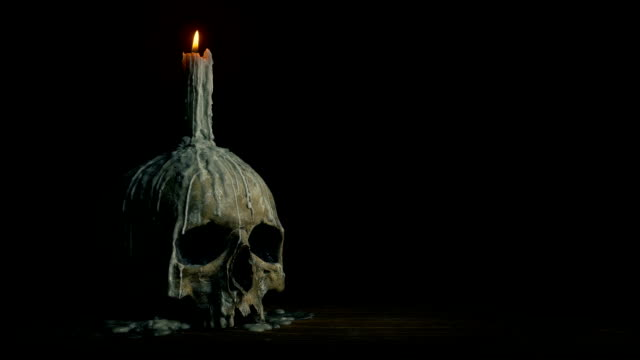 Passing Old Skull With Candle Melted On It Tracking shot moving slowly past an old skull with candle on it count dracula stock videos & royalty-free footage