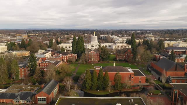 passing over willamette university with oregon pioneer atop the capital building salem - capitello video stock e b–roll