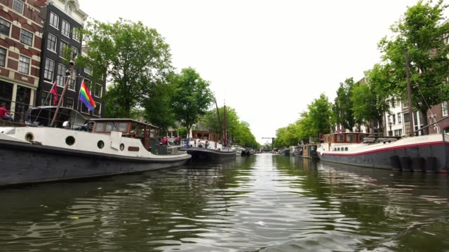passing the boat with rainbow flag in Amsterdam, Holland Europe