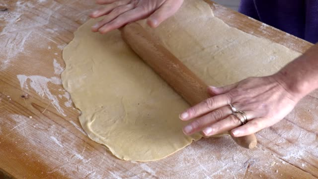 passing the wooden rolling pin on fresh dough passing the wooden rolling pin on fresh dough cooking utensil stock videos & royalty-free footage