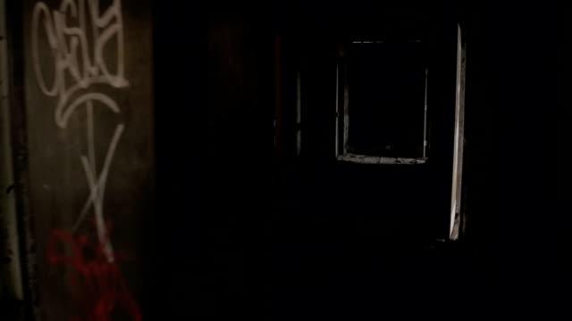 FPV Passing through dark spooky narrow hallway following weathered rotting doors