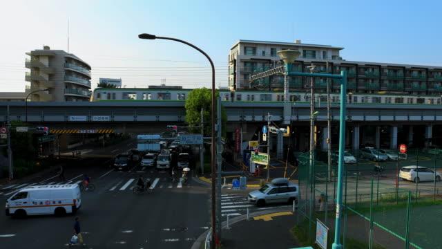 Ein vorbeifahrender Zug auf der Bahnstrecke an der Kanpachi Avenue in Tokio tagsüber – Video