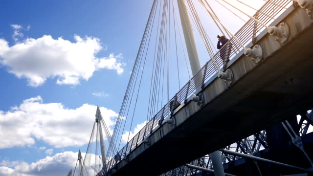 passing under foot bridge with sun glow - sotto video stock e b–roll