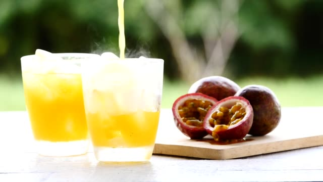 passion fruit juice on wooden table with green nature background - passiflora video stock e b–roll
