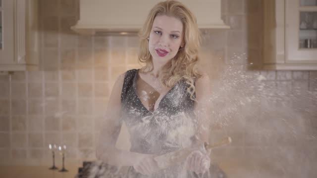 vidéos et rushes de fille passionnée dans la robe de soirée souillée dans la farine retenant un rouleau à pâtisserie dans sa main restant près de la table dans la cuisine. - rouge à lèvres rouge