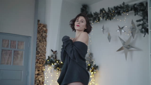 Passionate lady poses in decorated room and turns to camera video