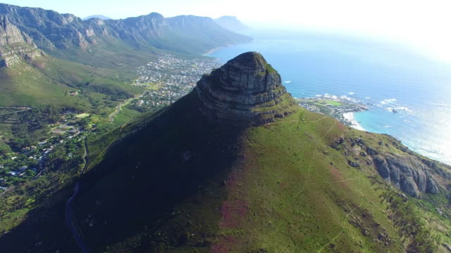 Past Lion's Head and on to Camps Bay Aerial drone footage of Lion's Head and Camps Bay in Cape Town, South Africa western cape province stock videos & royalty-free footage