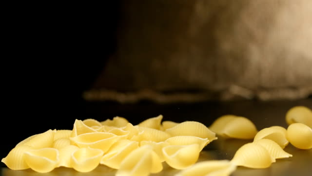 SLOW MOTION: Pasta (conchiglie) fall near a cloth bag SLOW MOTION: Pasta (conchiglie) fall near a cloth bag sac stock videos & royalty-free footage