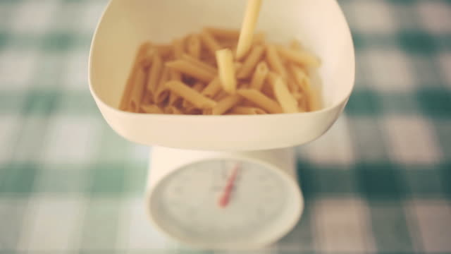 pasta falling in weight scale pasta falling in weight scale. uncooked pasta stock videos & royalty-free footage