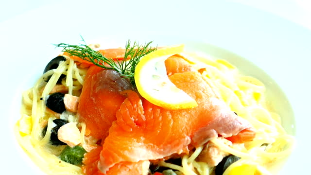 Pasta or Spaghetti cream sauce with salmon meat and lemon on top video