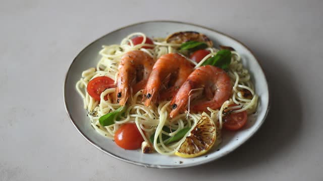 Pasta spaghetti with shrimp, tomatoes, garlic, spinach and lemon. Italian cuisine. Seafood. Diet.