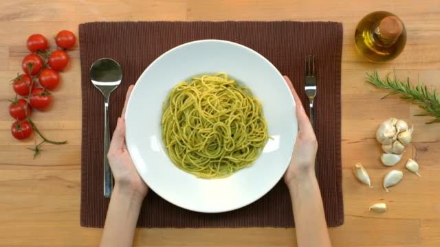 Pasta Fresh, cooked pasta, served on a plate. Top view of decorated table with tomatoes, garlic, olive oil, rosemary. Serving spaghetti with pesto on a plate. Decorating it with one leaf of parsley. pesto sauce stock videos & royalty-free footage