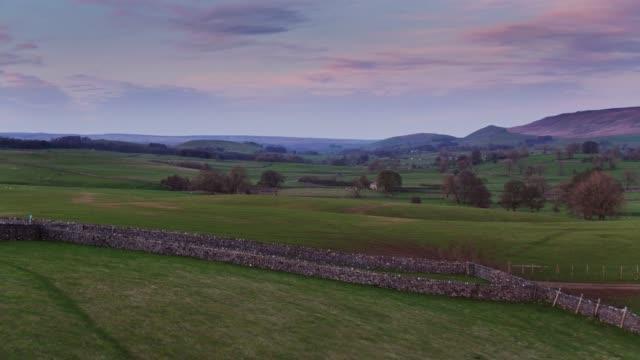 ヨークシャー ・ デイルズ - ドローン ショット夕日のパステル色 - 石垣点の映像素材/bロール