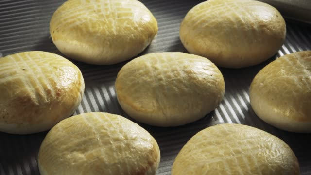 Pastry buns baking in time lapse on a gray baking pan bun bread stock videos & royalty-free footage