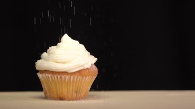 teig auf die cupcake puderzucker besprüht. slow-motion - zuckerguss stock-videos und b-roll-filmmaterial