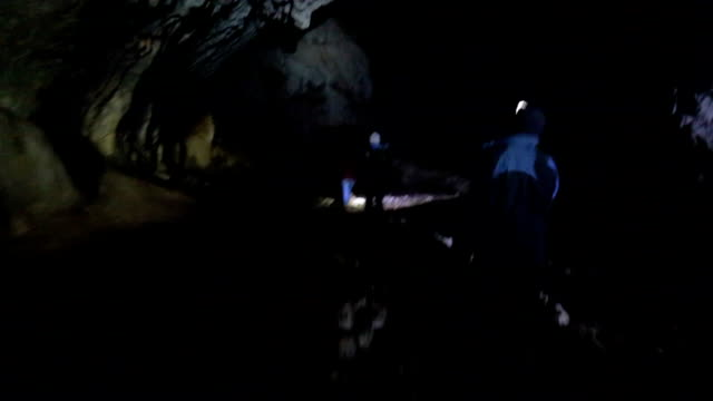 Path in the cave Group of young people exploring dark caves. archaeology stock videos & royalty-free footage