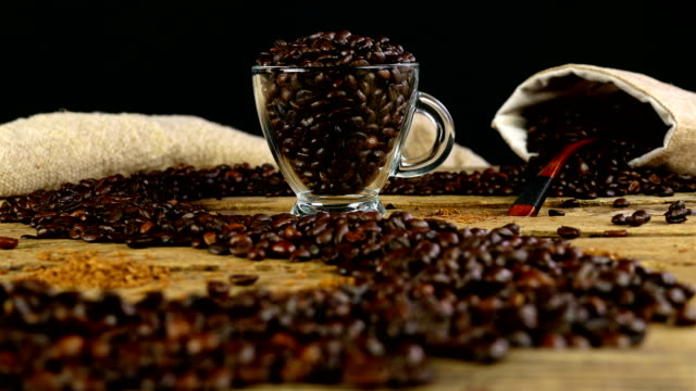 Path made with coffee beans on wooden table, cup and bag with coffee beans on background, dolly Path made with coffee beans on wooden table, cup and bag with coffee beans on background, dolly hot pockets stock videos & royalty-free footage