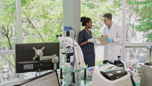 ラボ ウィンドウの横で会話をする病理学者と技術者 - 研究所点の映像素材/bロール