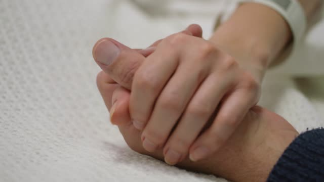 CU Patient and Visitor Holding Hands Close up of the hand of a female patient lying in a hospital bed being held by the hands of a Caucasian male visitor nhs stock videos & royalty-free footage