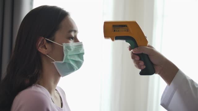 patient asiatisk kvinna ansikte och läkare hand med termometer kontrollera temperaturen - corona test bildbanksvideor och videomaterial från bakom kulisserna
