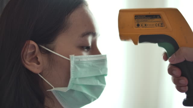 Patient Asian woman face and doctor hand with thermometer check temperature