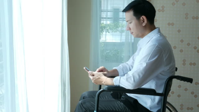 patient businessman sit on wheelchair , using phone patient businessman sit on wheelchair , using phone depression land feature stock videos & royalty-free footage