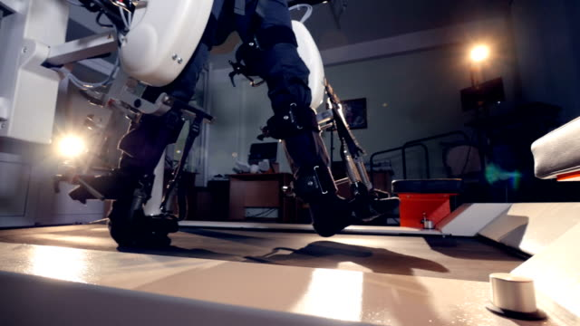 A patient going through robot-assisted training therapy. A patient going through robot-assisted training therapy. Legs close up. cyborg stock videos & royalty-free footage