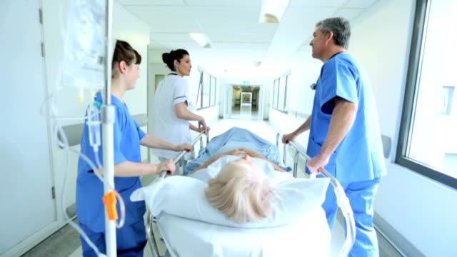 vídeos de stock, filmes e b-roll de paciente hospital cama movido pela equipe médica câmera lenta - geriatria