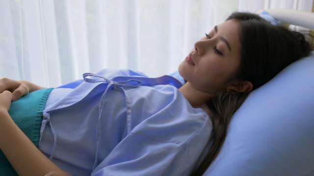 vídeos de stock e filmes b-roll de patient in hospital with saline solution volumetric infusion pump sleeping on examination couch. - melhoria