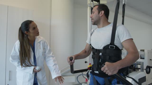 理学療法士によって導かれるトレッドミルの外骨格ロボットとの練習をする理学療法の患者 - 四肢点の映像素材/bロール