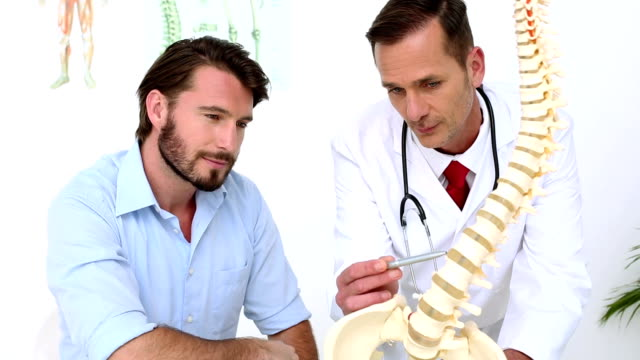 Patient listening to doctor explain spine model video