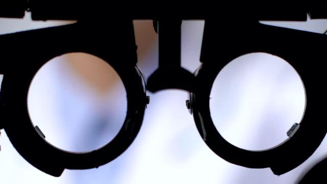 vidéos et rushes de patient regardant par le phoropter sur l'examen de vision, clinique ophtalmologique - réfracteur