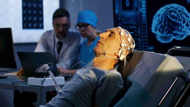 Patient lying in bed during EEG examination Rack focus shot from display screen with brain scan image to elderly patient lying in bed during EEG examination electrode stock videos & royalty-free footage