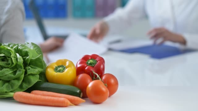 Patient meeting a dietician in the office Patient meeting a professional dietician in the office and receiving a prescription diet, healthy fresh vegetables on the foreground nutritionist stock videos & royalty-free footage