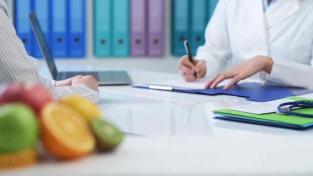 Patient meeting a nutritionist in the office Patient meeting a professional nutritionist in her office, the doctor is giving her a prescription diet and medical advice nutritionist stock videos & royalty-free footage