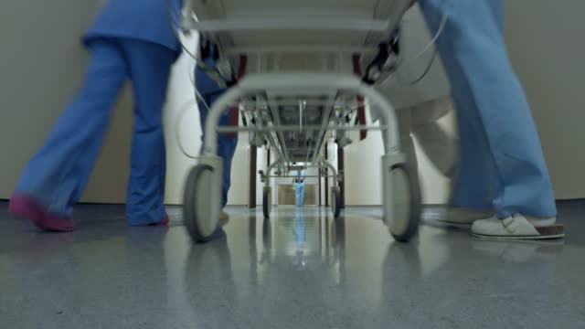 POV Patient on a stretcher being transported down the hospital hallway Point of view low angle shot of a patient on stretcher being transported down the hospital hallway by the medical team. hospital gurney stock videos & royalty-free footage