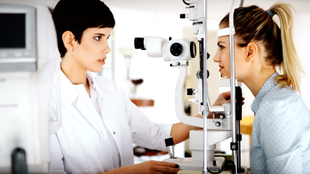 Patient or customer at slit lamp at optometrist or optician Patient or customer at slit lamp at optometrist or optician examining eyesight eye exam stock videos & royalty-free footage