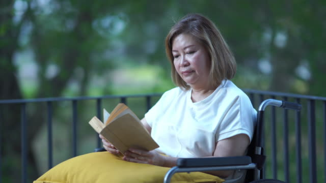 patient senior business woman reading book  on wheelchair