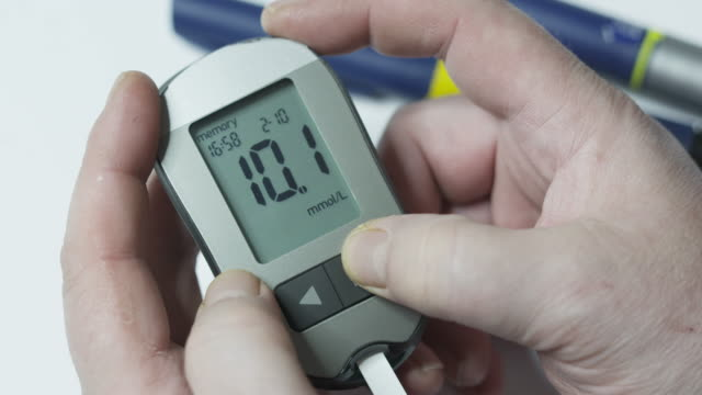 Patient with diabetes using blood glucose meter. Viewing blood glucose results video