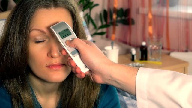 stockvideo's en b-roll-footage met geduldige vrouwengezicht en artsenhand met thermometercontroletemperatuur - thermometer
