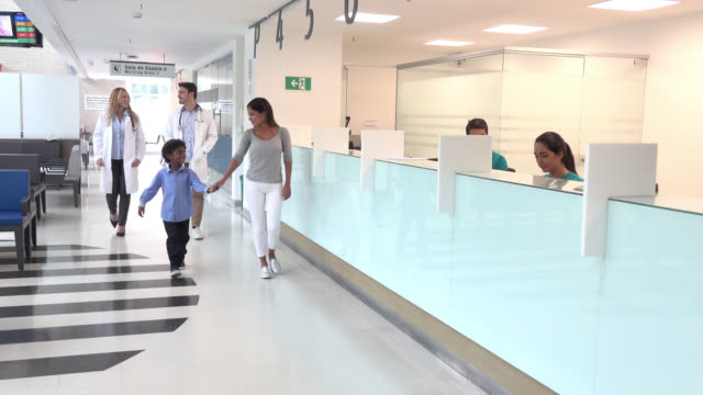 Patients and doctors walking through the corridor of a hospital Patients and doctors walking through the corridor of a hospital passing through the reception where there are more people working medical building stock videos & royalty-free footage