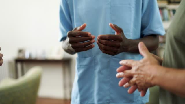 vídeos y material grabado en eventos de stock de pacientes en el asilo de ancianos hablando con enfermera masculina negra - geriatría