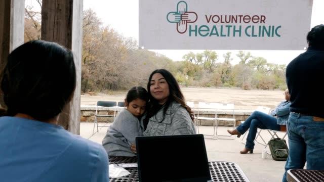 i pazienti vedono medici e infermieri in una clinica all'aperto gratuita - clinica medica video stock e b–roll