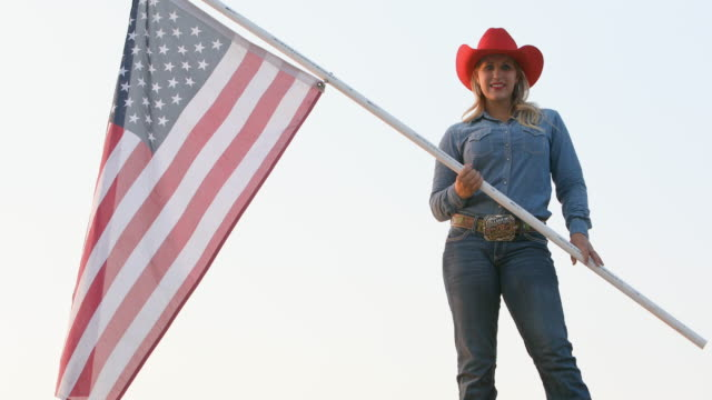 Patriotic Cowgirl Waving an American Flag Patriotic young woman cowgirl waving an American flag cowgirl stock videos & royalty-free footage
