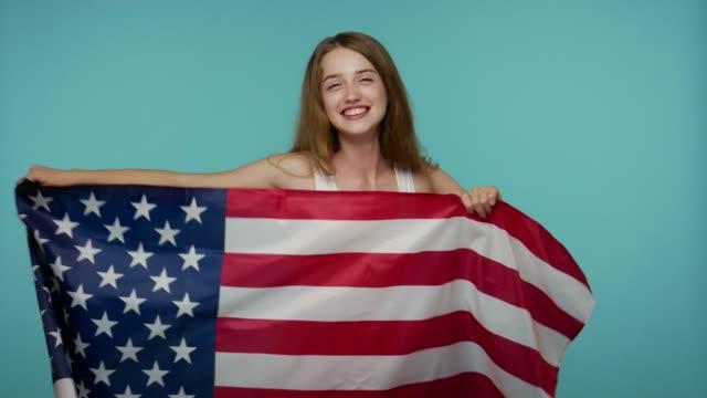 愛國女孩溫柔的外表揮舞著美國國旗, 開心地笑, 慶祝人權 - happy 4th of july 個影片檔及 b 捲影像